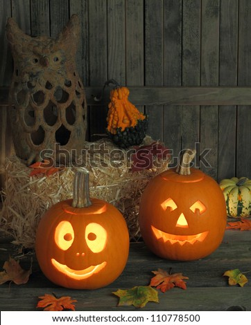 Two smiling jack-o-lanterns on a wooden deck