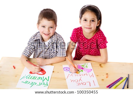 Two smiling kids at the table draw with crayons for mum, isolated on white