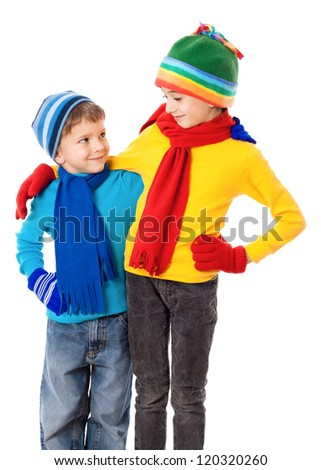 Two smiling kids in winter clothes standing together, isolated on white