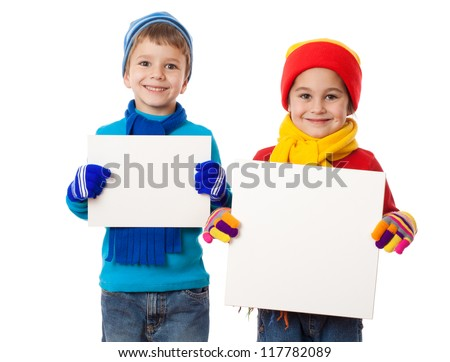 Two smiling kids in winter clothes standing with empty blank in hands, isolated on white