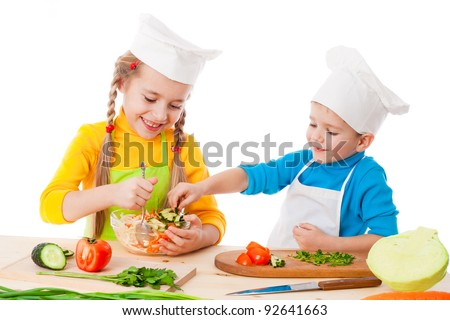 Two smiling kids mixing salad, isolated on white