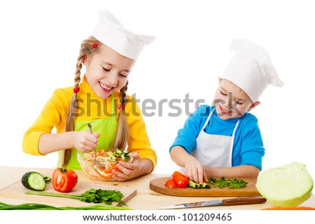 Two smiling kids mixing vegetable salad, isolated on white