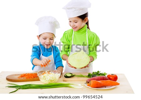 Two smiling kids preparing salad, isolated on white