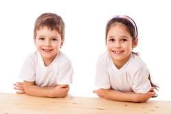 Two smiling kids sitting at the empty table and looking to camera, isolated on white