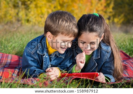 Two smiling kids with tablet pc on the autumn landscape, outdoors - stock photo