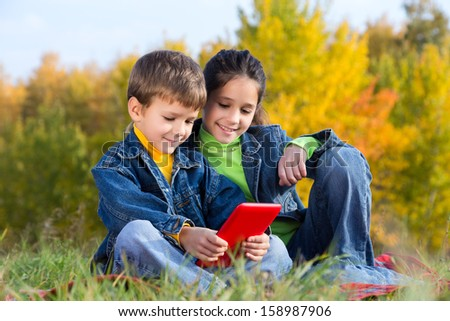 Two smiling kids with tablet pc sitting on the autumn lawn, outdoors