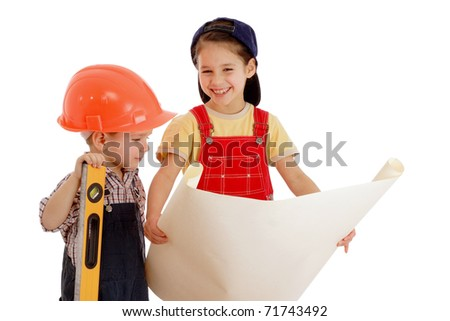 Two smiling little builders planning with liquid level and blueprint, isolated on white
