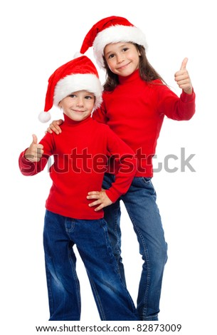 Two smiling little children with thumbs up sign and Santa's hats, isolated on white