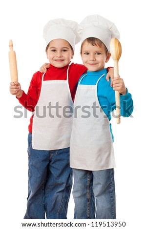 Two smiling little cooks with ladle and rolling pin, isolated on white