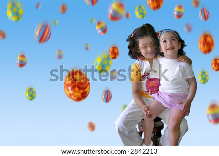 Two smiling little girls under a colorful Easter eggs rain.