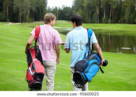 Two smiling men on a golf course