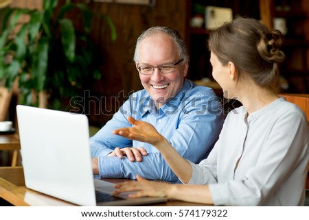 Two Smiling People Discussing Issues in Cafe