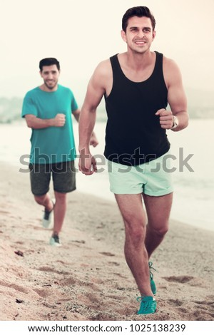 Two smiling sportsmen are jogging together on the beach near ocean