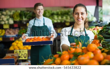 Two smiling supermarket workers in apron arranging citrus in fruit section