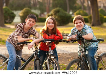 Two smiling teenage boys and one teenage girl having fun on bicycles in the park.