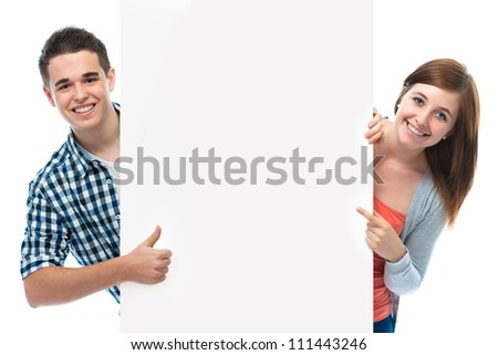 two smiling teenagers holding at a blank board
