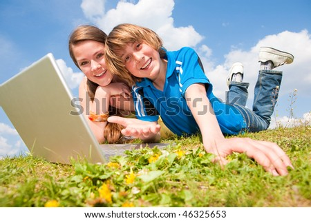Two Smiling teenagers with laptop resting on meadow. - stock photo