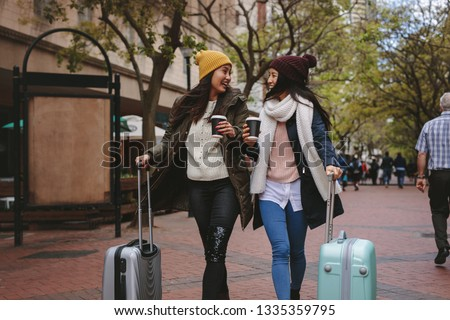 Two smiling woman tourists walking around the city drinking coffee. Two asian women walking on street with luggage bags enjoying coffee. Stock fotó ©