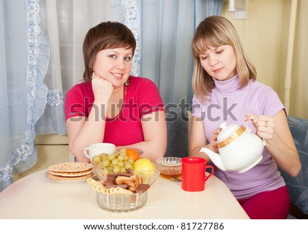 Two smiling women have tea in kitchen - stock photo