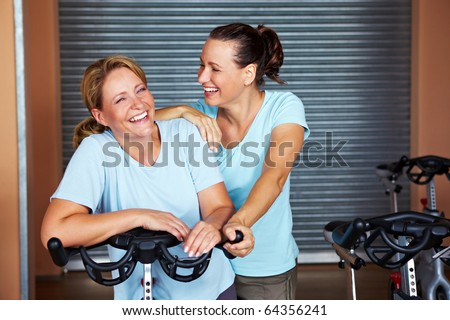 Two smiling women standing in room in a gym