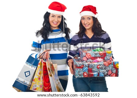 Two smiling women  wearing Santa hats and striped sweaters holding Christmas gifts  isolated on white background