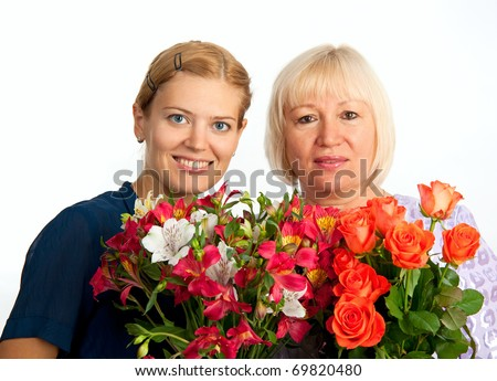 Two smiling women with flowers on white background - stock photo
