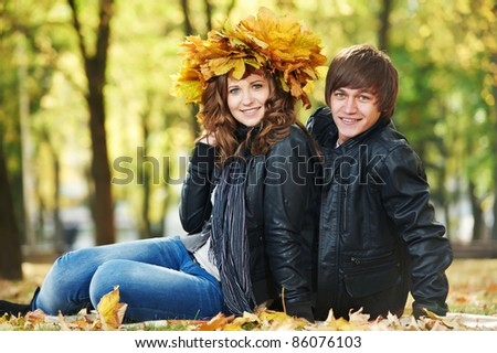 Two Smiling young attractive people with autumn maple leaves in park at fall outdoors date