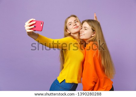 Two smiling young blonde twins sisters girls in colorful clothes doing selfie shot on mobile phone isolated on pastel violet blue wall background. People family lifestyle concept. Mock up copy space
