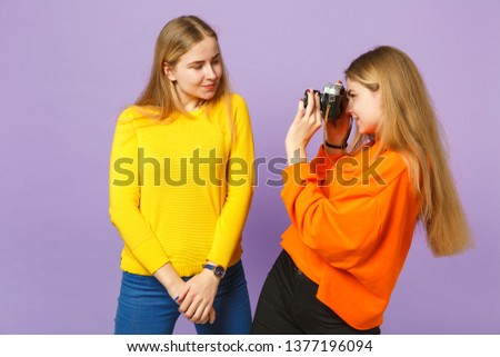 Two smiling young blonde twins sisters girls in colorful clothes taking pictures on retro vintage photo camera isolated on violet blue background. People family lifestyle concept. Mock up copy space