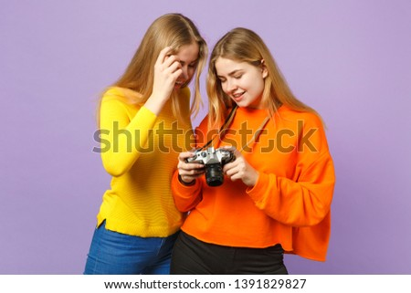 Two smiling young blonde twins sisters girls in vivid colorful clothes holding retro vintage photo camera isolated on violet blue wall background. People family lifestyle concept. Mock up copy space