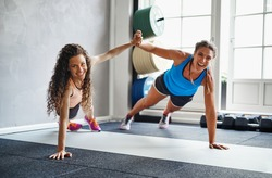 Two smiling young female friends in sportswear high fiving each other while doing pushups together on the floor of a gym