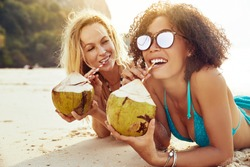 Two smiling young female friends wearing bikinis and drinking from coconuts while suntanning together on a sandy beach during a tropical vacation