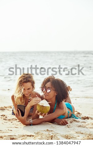 Two smiling young female friends wearing bikinis taking selfies and drinking from a coconut while suntanning on a sandy beach during a tropical vacation