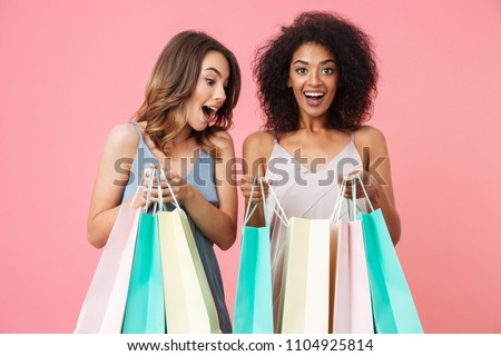 Two smiling young girls dressed in summer clothes looking inside shopping bags isolated over pink background