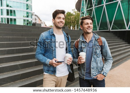 Two smiling young men friends dressed casually spending time together at the city, drinking takeaway coffee