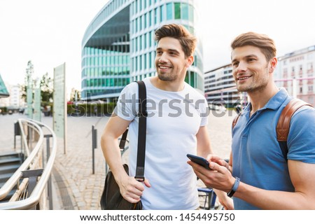 Two smiling young men friends dressed casually spending time together at the city, holding mobile phone