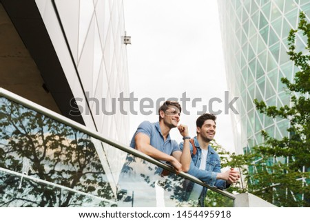 Two smiling young men friends dressed casually spending time together at the city, leaning on rail while standing and talking