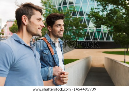 Two smiling young men friends dressed casually spending time together at the city, walking