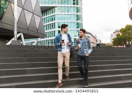 Two smiling young men friends dressed casually spending time together at the city, walking down the stairs