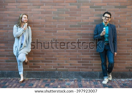 Two smiling young people holding ice cream cones standing apart near brick wall with copy space