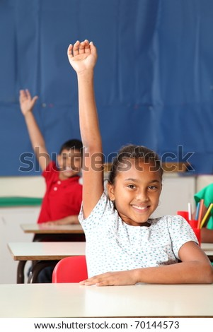 Two smiling young school children arms raised in class
