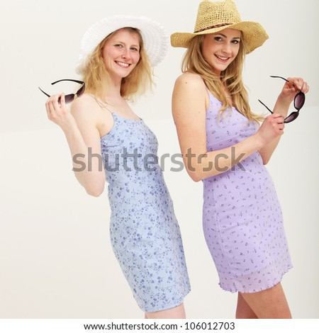 Two smiling young women wearing sun hats and holding sunglasses.