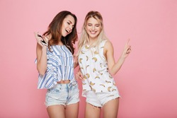 Two smiling young women with earphones listening to music from mobile phone over pink background
