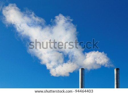 two smoking chimneys on blue sky background