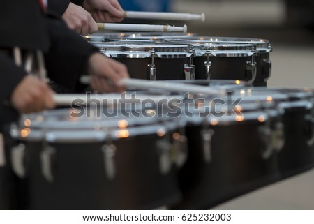 two snare drummers warming up before the bands performance at a football game