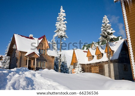 Two snow-covered wooden at home in Carpathian Mountains, Ukraine, Dragobrat
