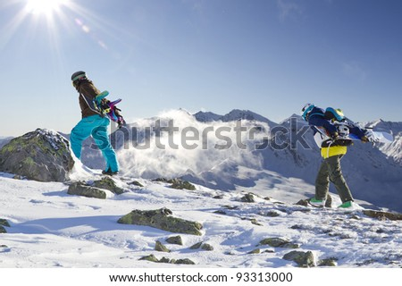 Two snowboarder climbing up the mountain