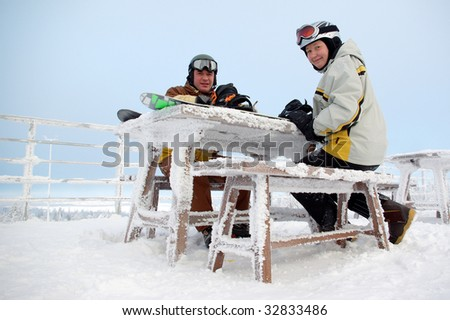 Two snowboarders and snow covered bench