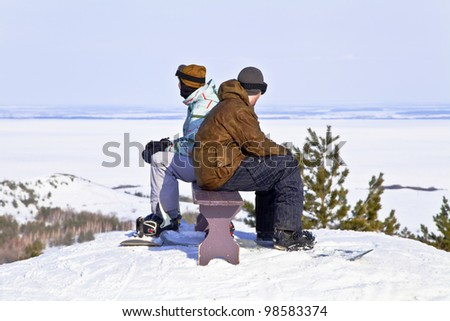 Two snowboarders resting on top of mountain against the backdrop of a beautiful winter landscape. Back to back.