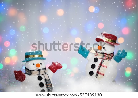 Two snowman playing snow on bokeh background with copy space for season greeting Merry Christmas or Happy New Year,  #537189130